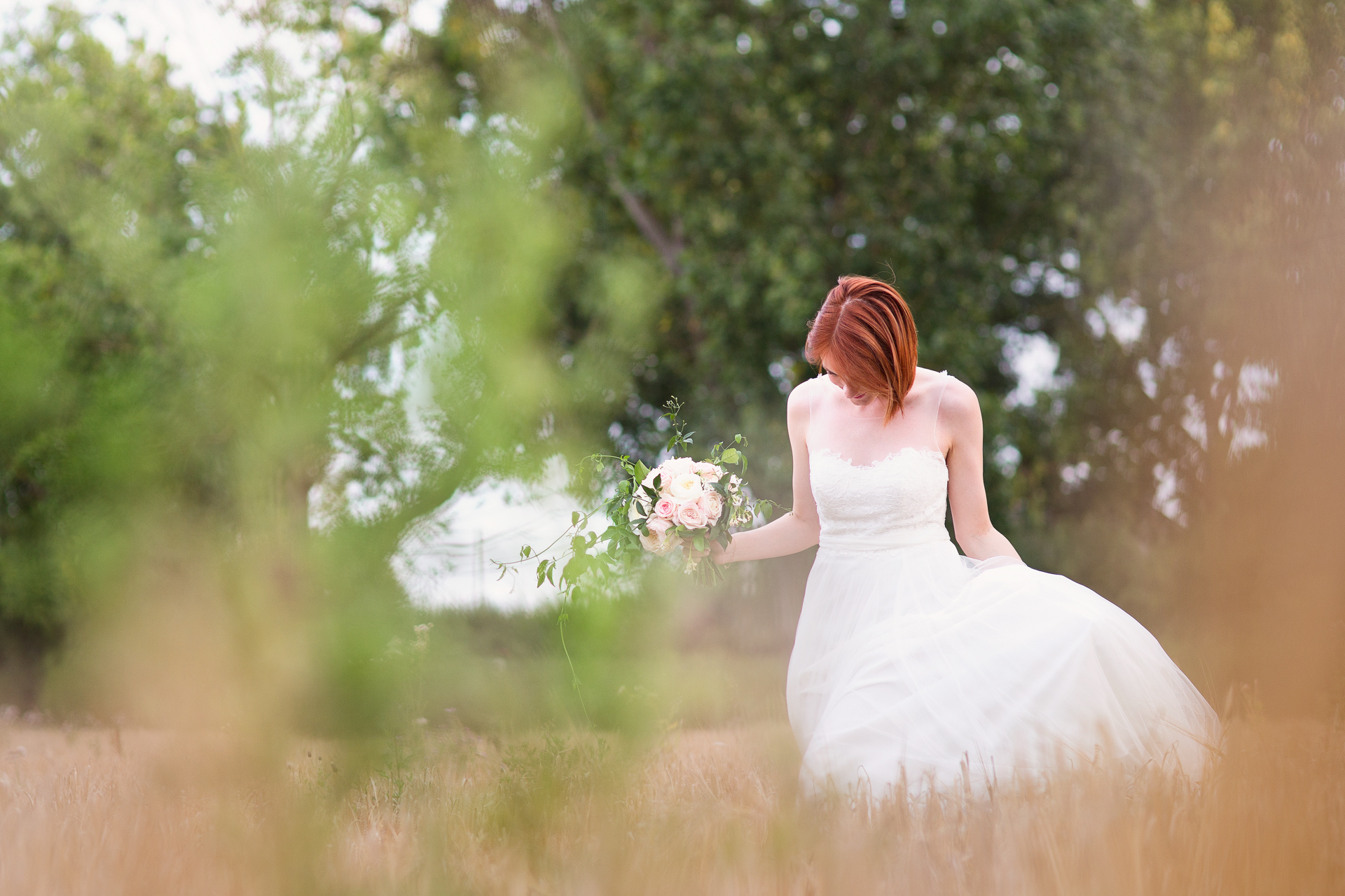 Bride walking through a field of reeds in Colchester at her wedding at The Barn Brasserie