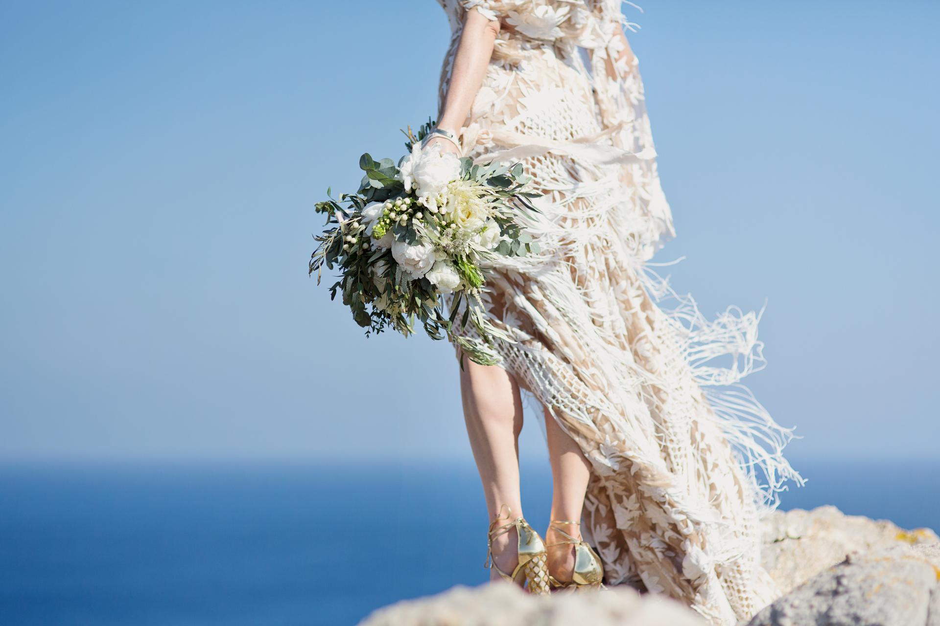 rue de seine bridal gown in the wind on a cliff top in mykonos