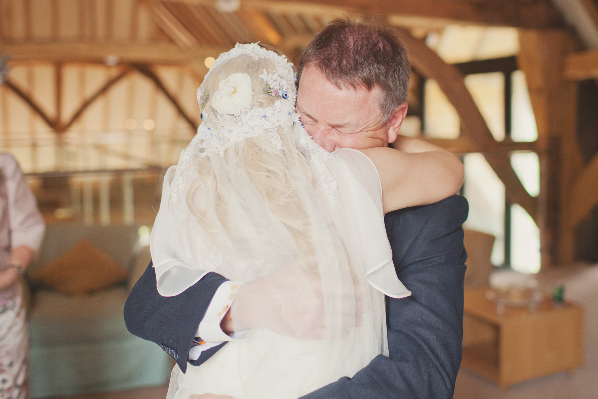 father embraces daughter on her wedding day